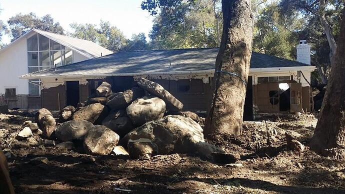 Photo of a mud-covered home with leaning trees, and large boulders deposited in the yard