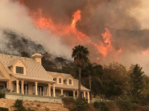 Photo of a large home left untouched by intense flames burning around it