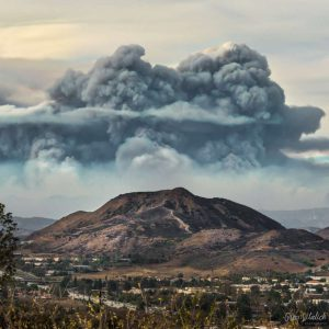 photo of massive gray and black mushroom cloud of smoke dwarfs the mountains behind a town.