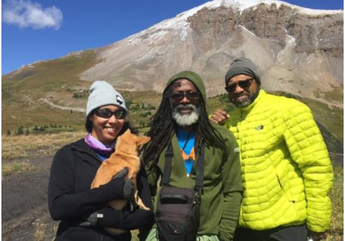 Three Black people wearing sunglasses, jackets, and knit caps are standing facing the camera on a mountain trail. A young woman on the left holds a small dog with golden fur, The man in the center has long dark hair and a gray beard. He is wearing a dark green hooded jacket and carrying a satchel around his neck. The man on the left is the tallest and is wearing a bright yellow down jacket.