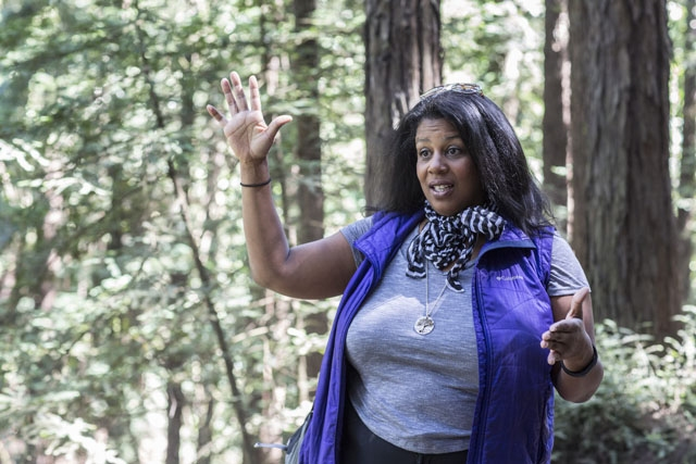 A Black woman wearing a gray t-shirt and a purple vest with a striped scarf around her neck is standing in a forest and gesturing with her hands. Her right arm is raised, bent at a right angle at the elbow with her palm facing forward. Her left arm is at her side, also bent in a right angle at the elbow, with her palm facing left.
