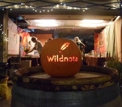 A lighted pumpkin carved with the word wildnote and the company's feather logo