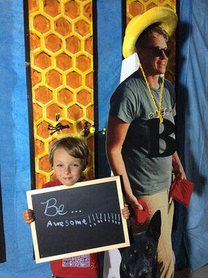 "A child holding a sign that says ""Be Awesome"" next to a life-size cutout of Wildnote CEO Kristen Hazard"