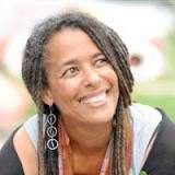 head shot of smiling black female environmentalist with long braided hair looking up and to her left.