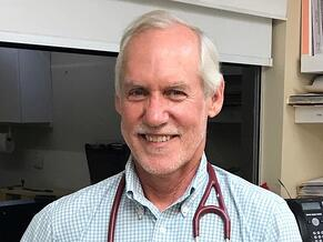 A gray-haired man wearing a blue and white checked shirt, and a stethoscope around his neck, is smiling at the camera.