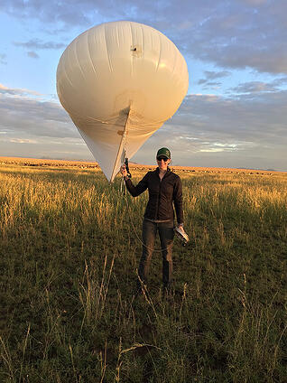 Researcher Lacey Huey holding a tethered aerostat to collect aerial images.