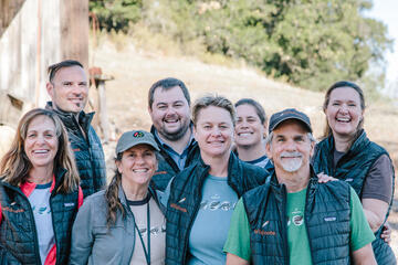 Group of five women and three men smiling and wearing vests bearing the Wildnote name and feather logo
