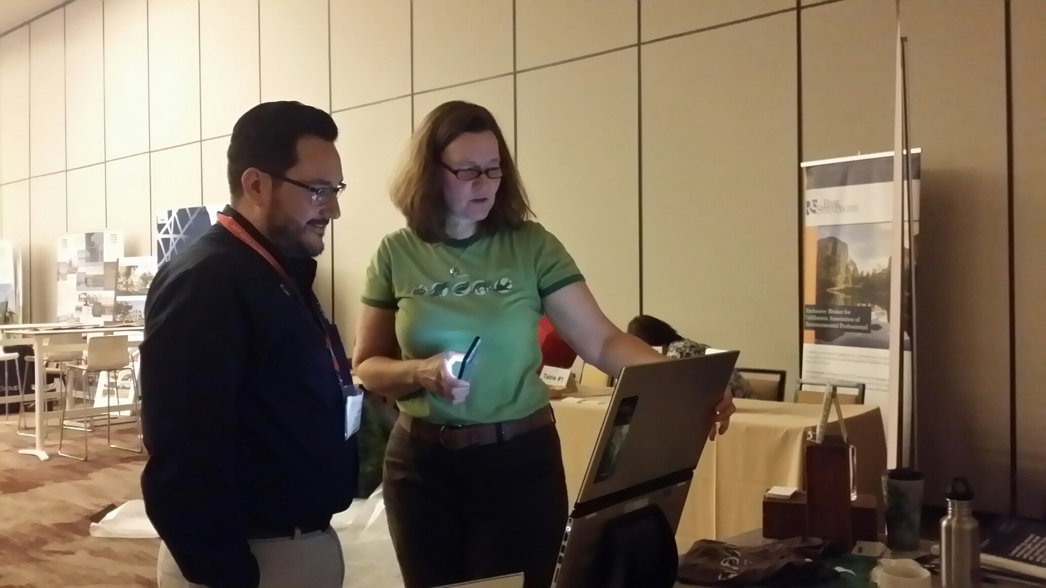 A woman and a man are standing and  looking at a laptop computer screen